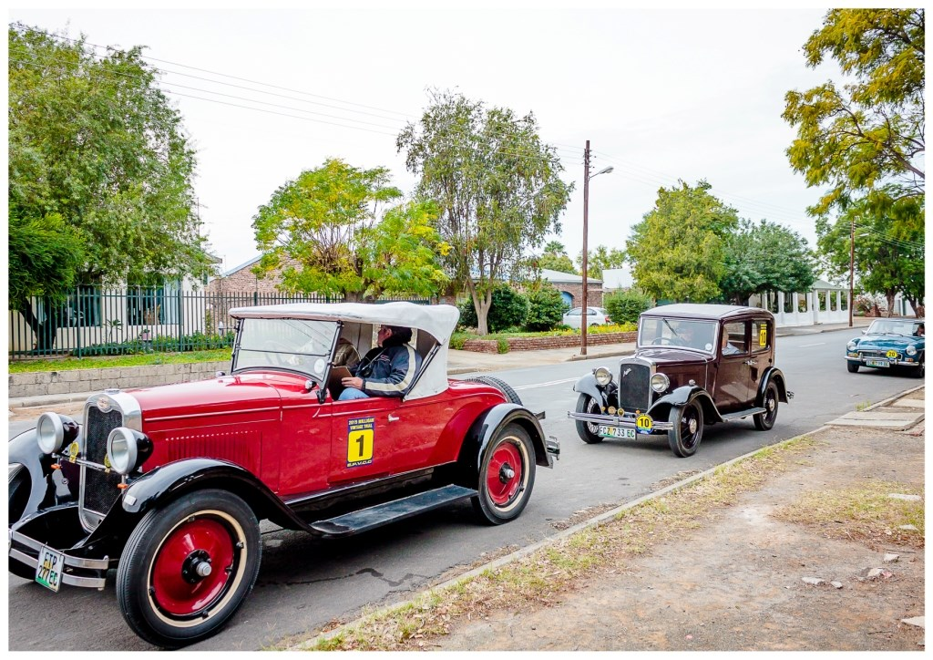 barney-marais-and-his-navigator-in-the-1928-chevrolet-lead-the-pack-through-the-streets-of-graaff-reinet